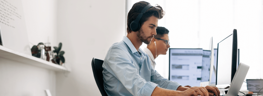 man in shirt wearing headphones working on a computer software development