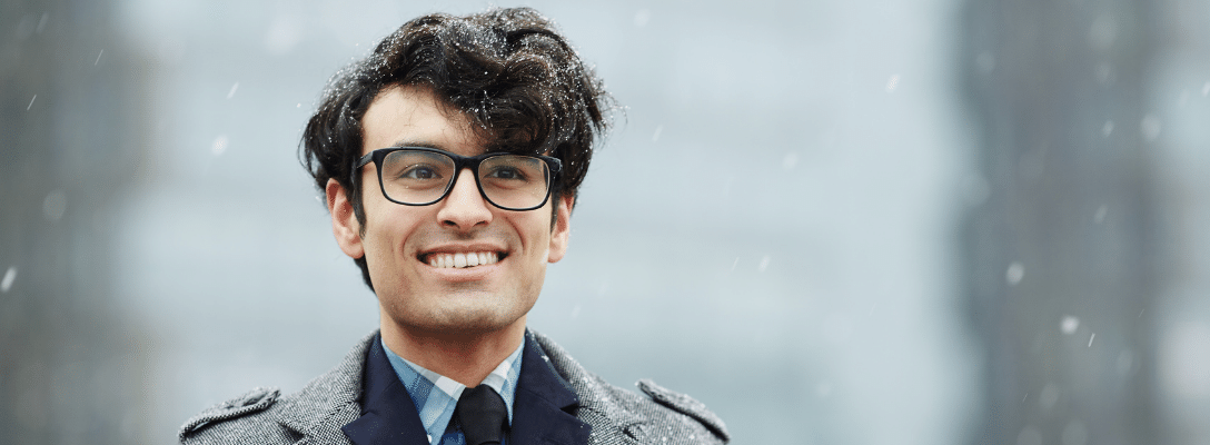 man wearing glasses in a shirt and overcoat in snow employee winter