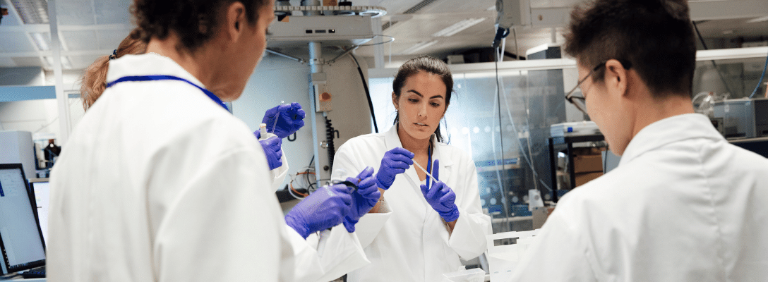 three people in lab coats women stem