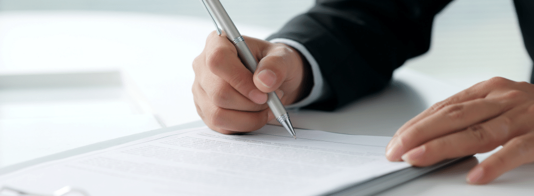 person in suit writing on contract on white desk