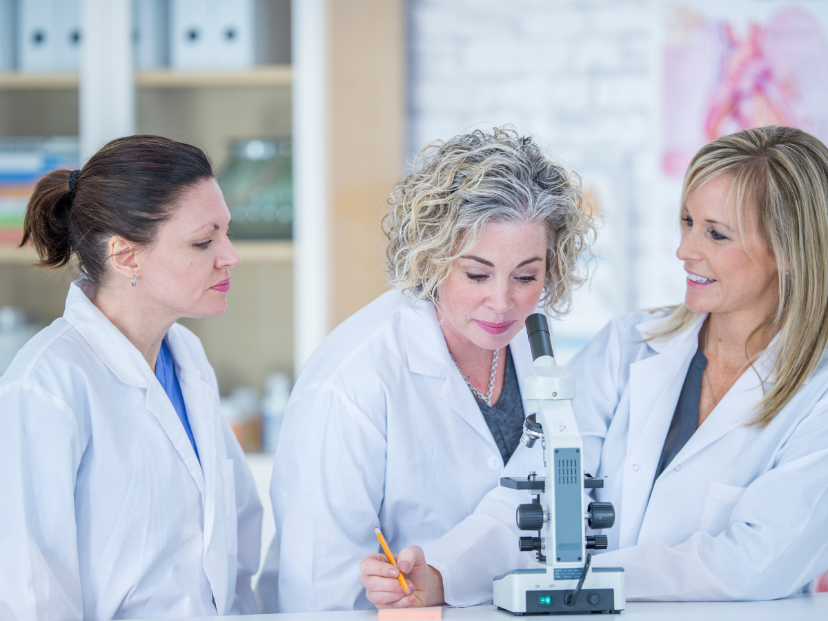 three women in labcoats working analysing through microscope life sciences